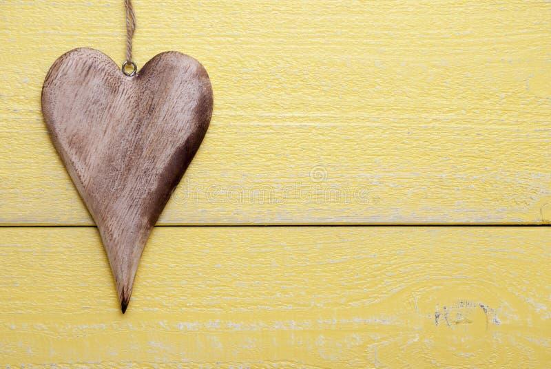 Ein Herz mit Kopien-Raum, gelber hölzerner Hintergrund stockbild