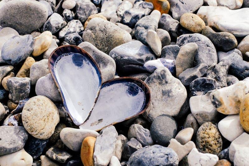 Ein Herz von Oberteilen auf einem Strand von Steinen stockfotografie
