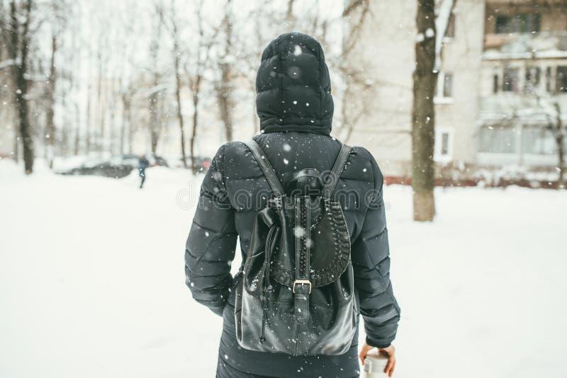 Ein hinterer Schuss eines schönen youngwoman gekleidet in einer schwarzen Winterjacke mit ledernen Rucksackwegen in der schneebed stockbilder
