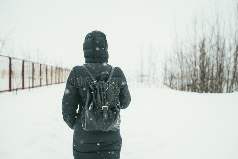 Ein hinterer Schuss eines schönen youngwoman gekleidet in einer schwarzen Winterjacke mit ledernen Rucksackwegen in der schneebed stockfotografie