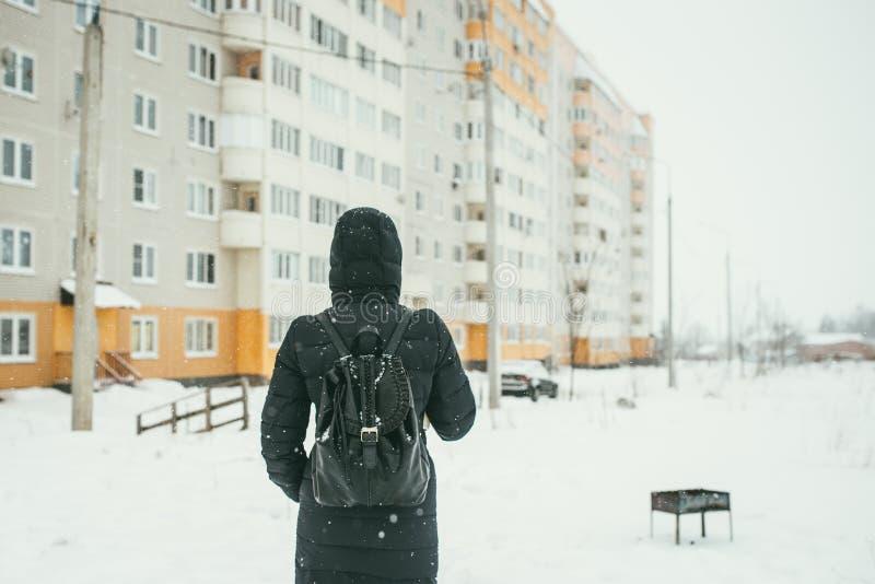 Ein hinterer Schuss eines schönen youngwoman gekleidet in einer schwarzen Winterjacke mit ledernen Rucksackwegen in der schneebed stockfoto