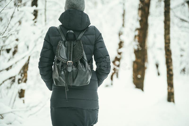 Ein hinterer Schuss eines schönen youngwoman gekleidet in einer schwarzen Winterjacke mit ledernen Rucksackwegen im schneebedeckt stockfoto