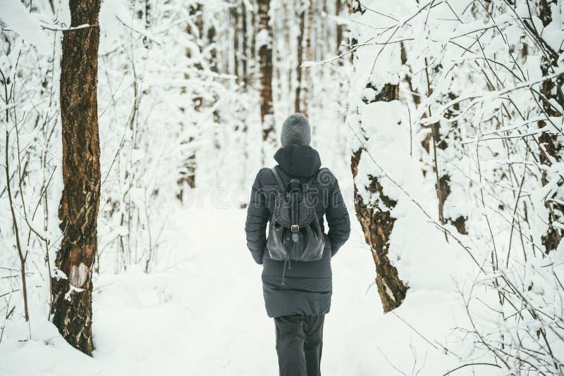 Ein hinterer Schuss eines schönen youngwoman gekleidet in einer schwarzen Winterjacke mit ledernen Rucksackwegen im schneebedeckt stockbilder
