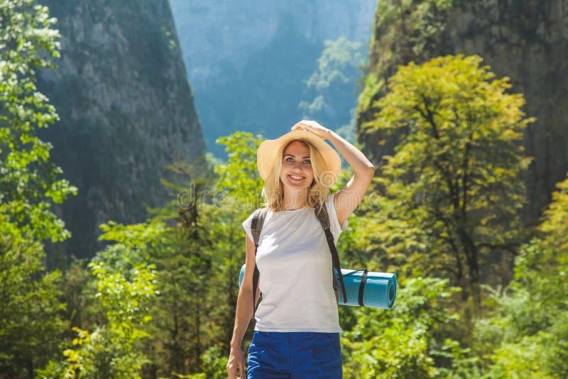 Ein Hippie-Mädchen in einem Hut reist in die Berge, die das Mädchen liebt zu reisen Ansicht von der Rückseite des touristischen R stockfotos