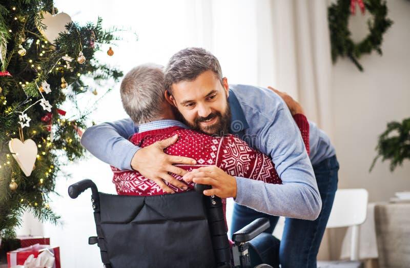 Ein Hippie-Mann, der seinen älteren Vater im Rollstuhl zur Weihnachtszeit umarmt stockbild