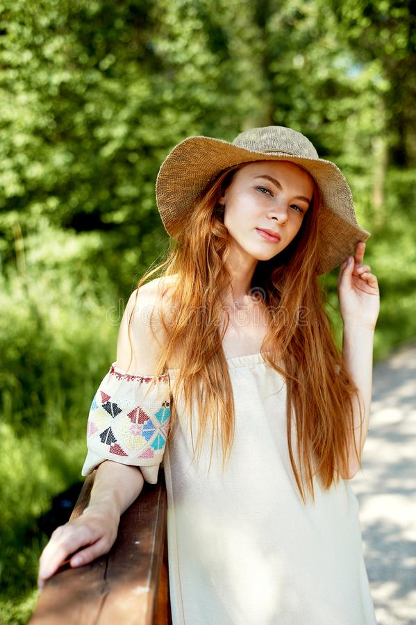 Ein hoch entwickeltes rothaariges Mädchen in einem einfachen Leinenkleid, in einem hellen breitrandigen Hut Vorbildlicher Blick N lizenzfreie stockbilder