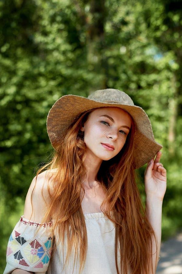 Ein hoch entwickeltes rothaariges Mädchen in einem einfachen Leinenkleid, in einem hellen breitrandigen Hut Vorbildlicher Blick N lizenzfreies stockfoto
