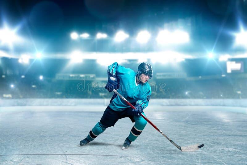 Ein Hockeyspieler, der mit Stock auf Eisarena eisläuft stockfoto