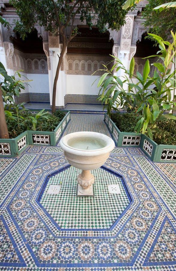Ein Hof mit einem Brunnen und einem Mosaikfliesenboden in einem Palast in Marokko stockfotos