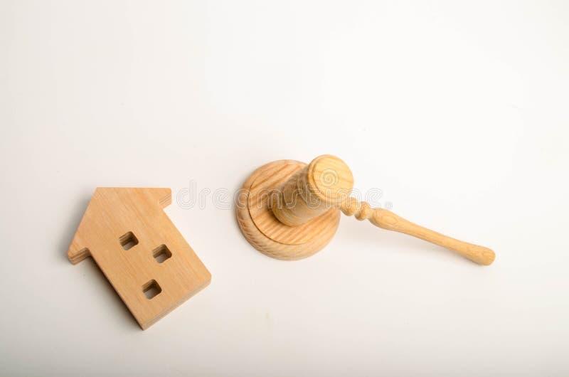 Ein Holzhaus und ein Hammer des Richters Rechtssachen auf Wohngebäuden Konflikt zwischen Nachbarn Demolierung von altem hous lizenzfreies stockfoto