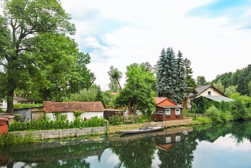 Ein Holzhaus zwischen großen alten Bäumen am Kanaldamm, blauen Kiefern und einem Kanu nahe dem Bretterzaun, ein Landschaft Landsc stockfotografie