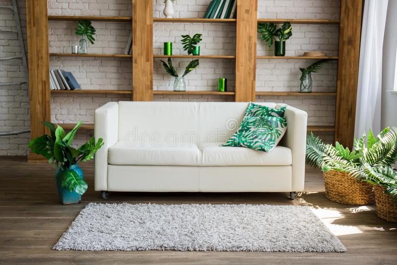Ein Holzregal mit weißem Sofa nahe bei ihm stockfoto