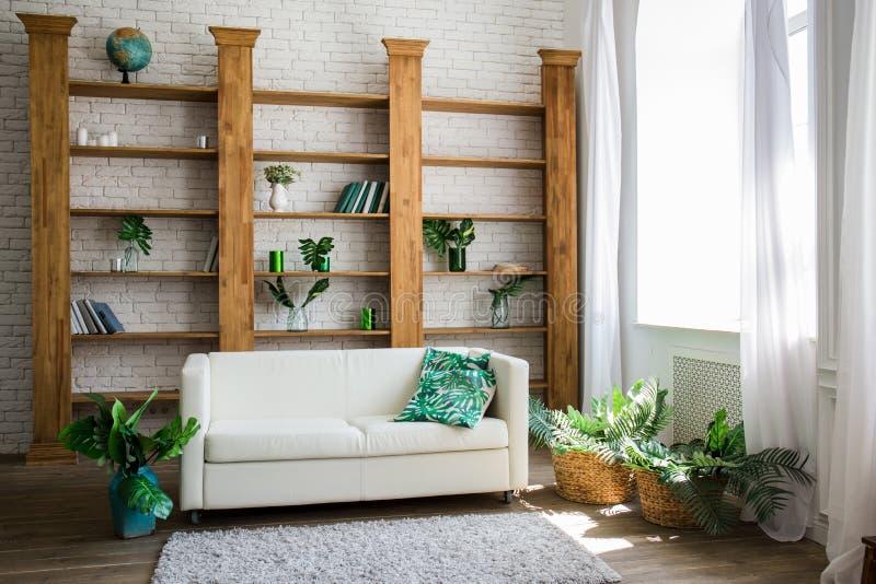 Ein Holzregal mit weißem Sofa nahe bei ihm lizenzfreies stockfoto