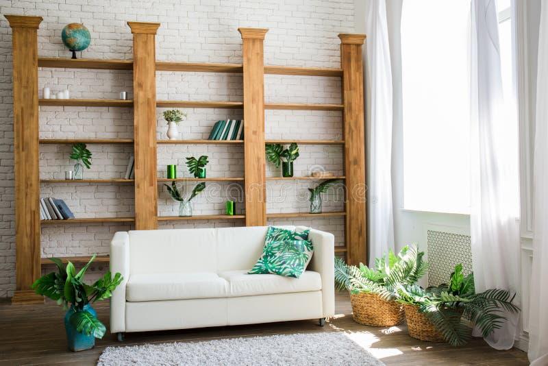 Ein Holzregal mit weißem Sofa nahe bei ihm stockbild