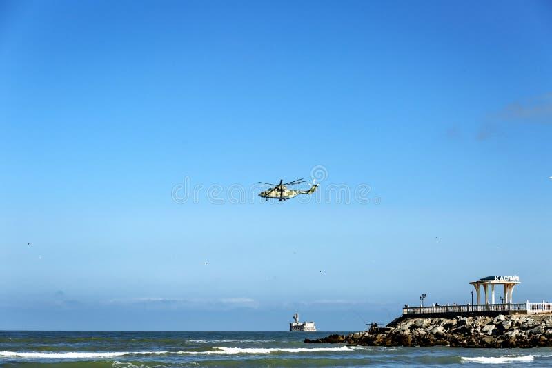 Ein Hubschrauber ?ber dem Meer und ein Gazebo mit einer Aufschrift in russischem Kaspiysk stockfotografie