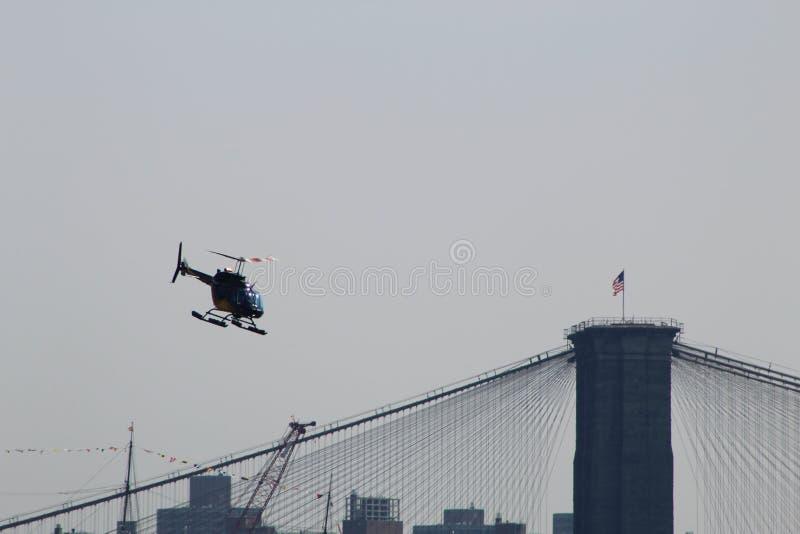 Ein Hubschrauberfliegen über der Brooklyn-Brücke lizenzfreie stockbilder
