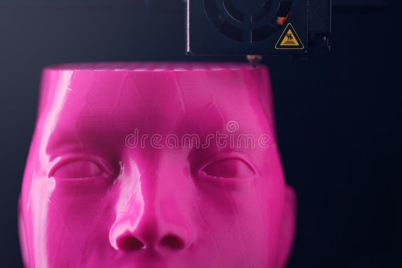 Ein humanoid Kopf wird durch ein 3D-printer vom rosa Plastik in unscharfem Licht hergestellt lizenzfreie stockfotos