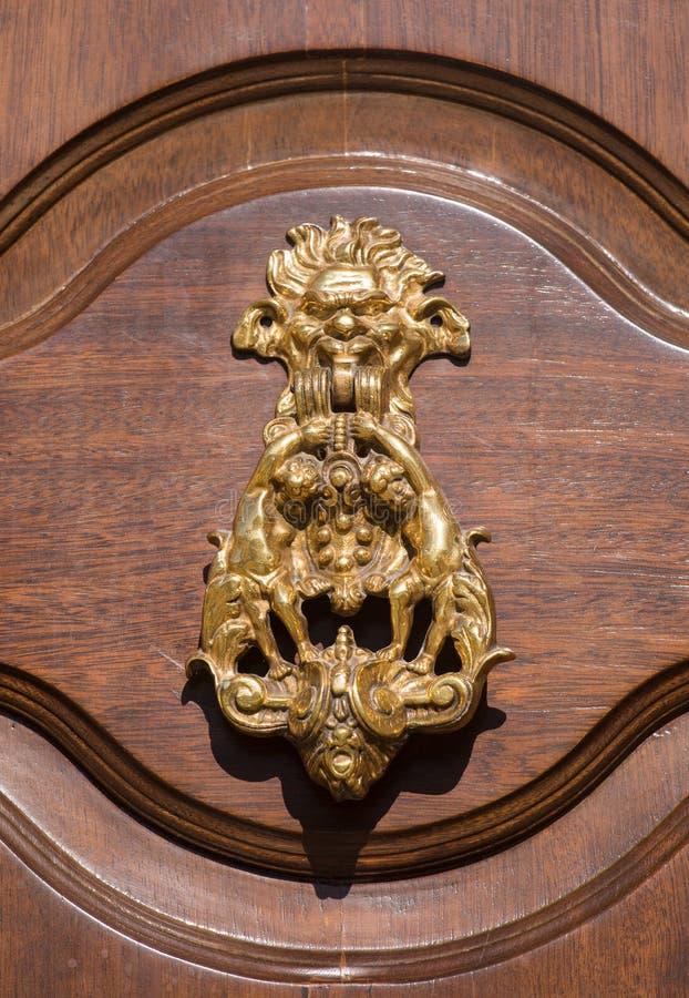 Ein im altem Stil dekorativer Bronzetürgriff auf einer Holztür, der Besonderheit und Symbol von Malta in Mdina stockbild