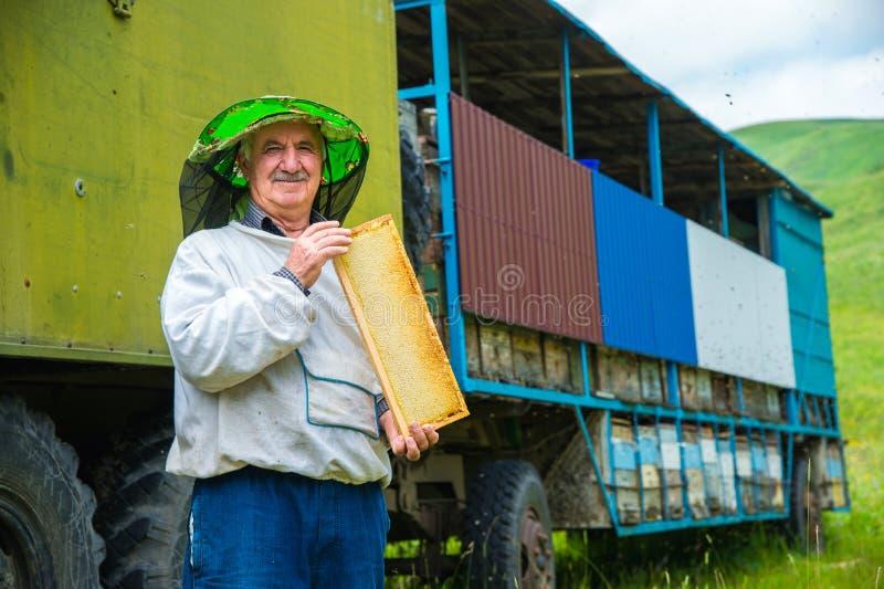Ein Imkermann hält einen Rahmen mit Bienenwabe-gefüllten Bienenwaben lizenzfreies stockbild