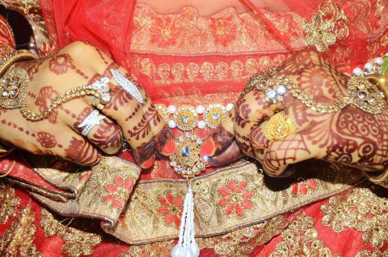 Ein indischer Bräutigam, der ihren goldenen Bauchgurt befestigt über Saree zeigt lizenzfreie stockfotografie