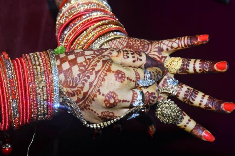 Ein indischer Bräutigam, der ihren goldenen Ring in ihrem schönen Schuss des Fingers zeigt stockbilder