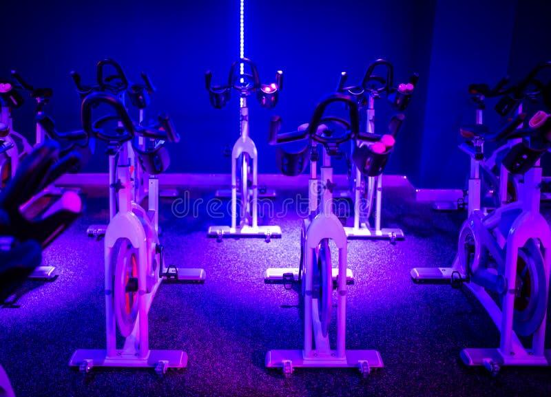 Ein Indoor-Radsport-Tanzkurs in einem blauen LED-Lichtraum lizenzfreie stockbilder