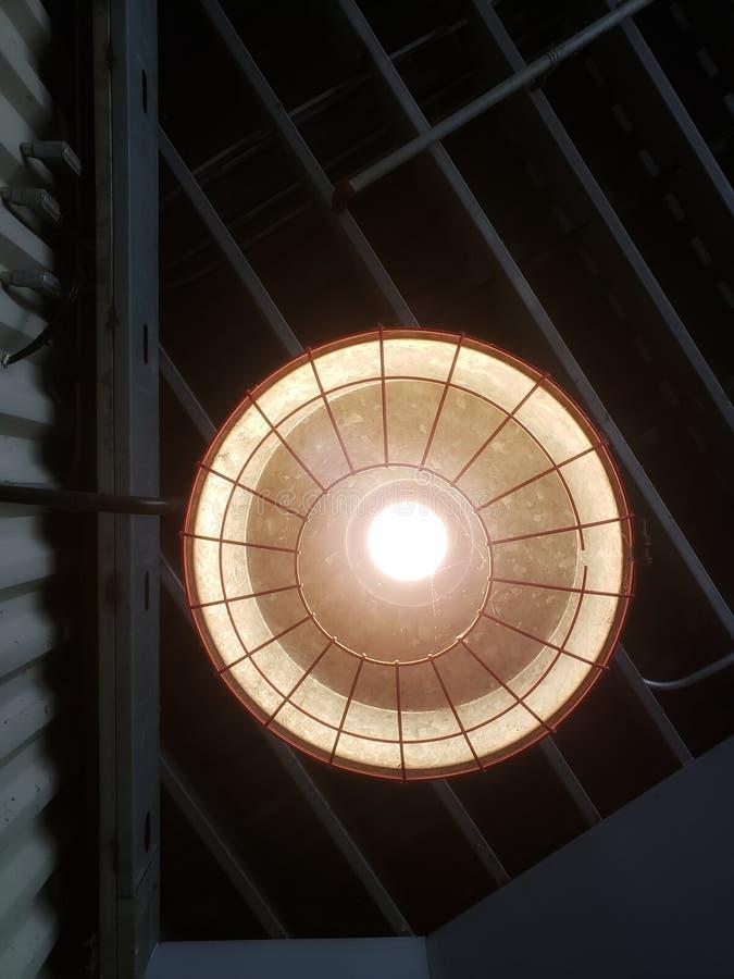 Ein industrielles Licht, das unten von unfertiger Lagerdecke glänzt stockfotografie