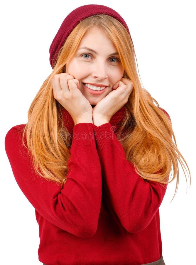 Ein Ingwermädchen im Lächeln und in den Griffen ihre Hände nahe dem Gesicht Getrennt auf weißem Hintergrund stockfotografie