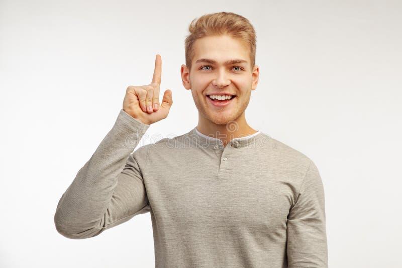 Ein intelligenter bärtiger Mann hebt seinen Zeigefinger an, während er eine gute Idee oder guten Nachrichten über eine erfolgreic lizenzfreie stockfotografie
