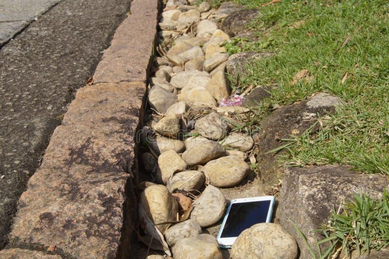 Ein intelligentes Telefon verlor längsseits von einer Straße stockbild