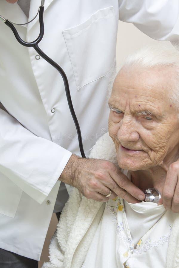 Ein Internistdoktor überprüft die Lungen einer sehr alten grauhaarigen Frau, die in einem Stuhl mit einem Stethoskop sitzt stockbilder