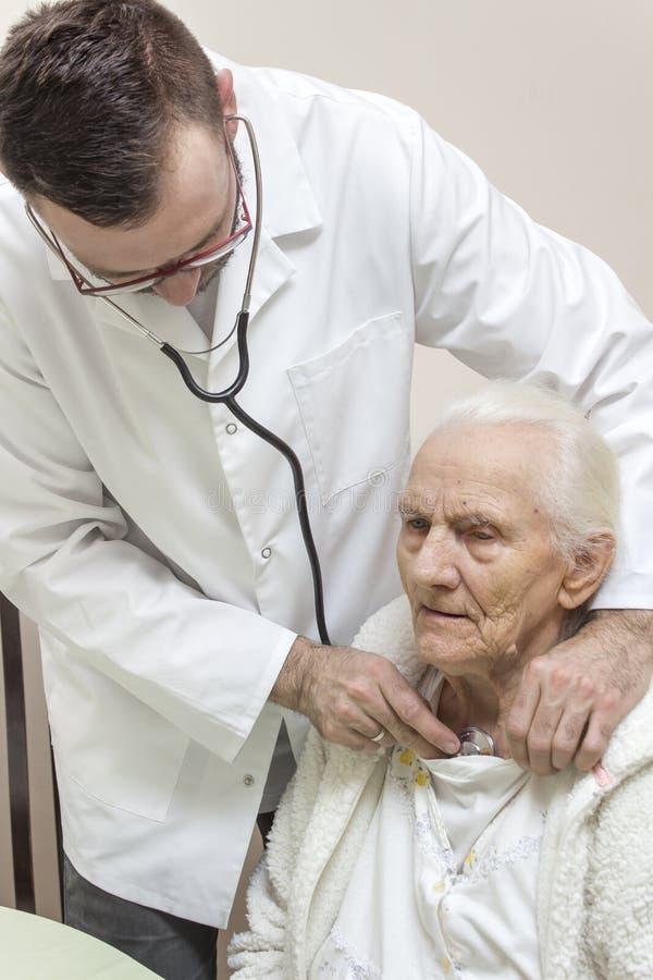 Ein Internistdoktor überprüft die Lungen einer sehr alten grauhaarigen Frau, die in einem Stuhl mit einem Stethoskop sitzt stockfotos
