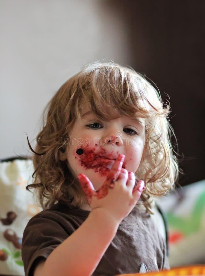 Ein jähriges Baby, das köstliche Blaubeer- und der Schwarzen Johannisbeeretorte mit ihrem Gesicht schmutzig isst lizenzfreie stockfotos