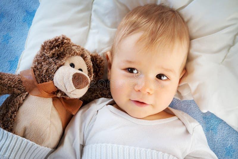 Ein jähriges Baby mit einem Teddybären stockbilder