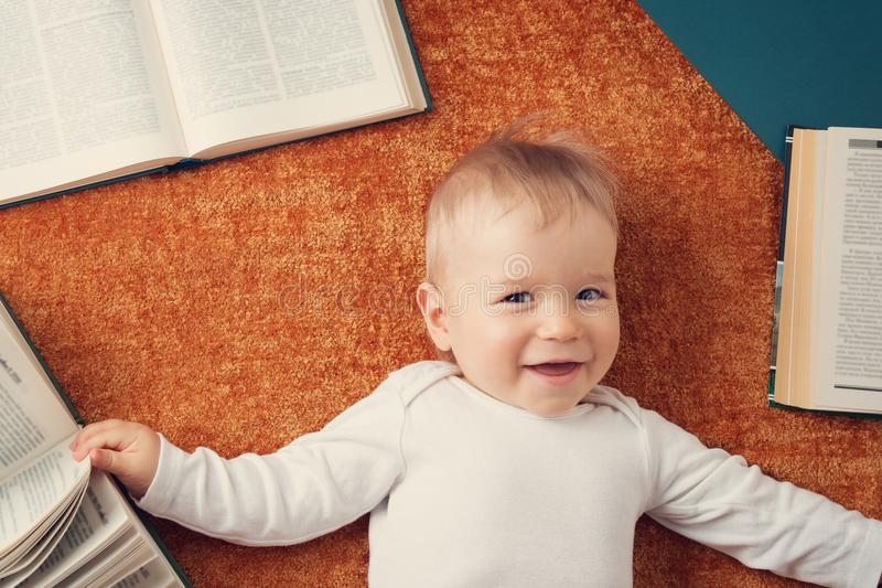 Ein jähriges Baby mit spectackles und Büchern stockfotografie