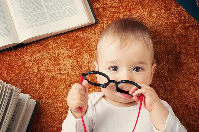 Ein jähriges Baby mit spectackles und Büchern lizenzfreie stockfotos