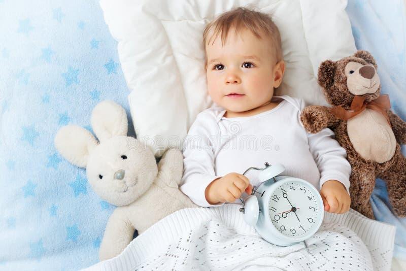 Ein jähriges Baby mit Wecker lizenzfreie stockfotografie