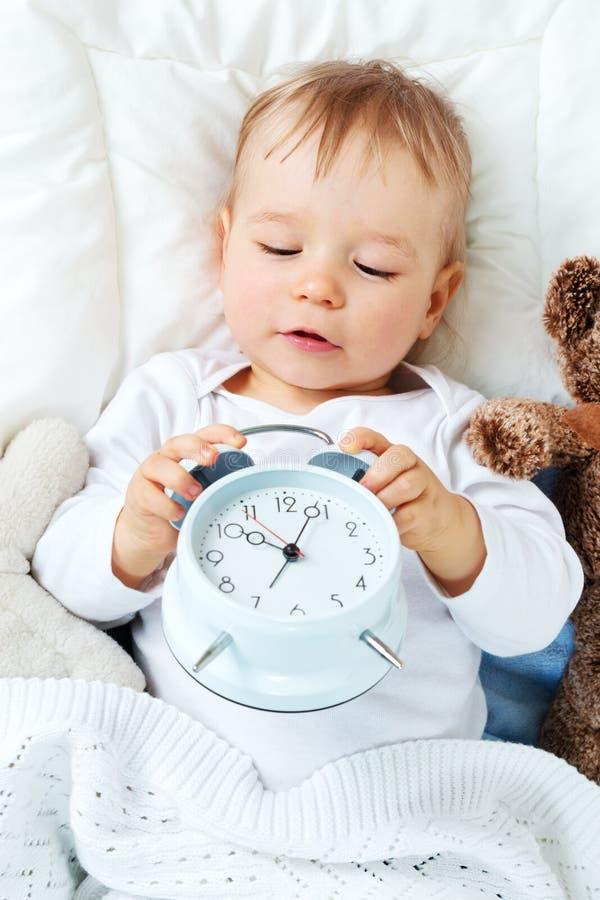 Ein jähriges Baby mit Wecker lizenzfreie stockbilder