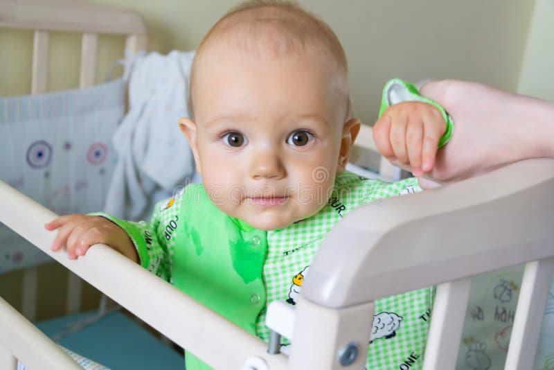 Ein jähriges Baby sitzt und schaut aufmerksam irgendwo Kleiner netter Junge in einer hellgrünen Klage mit Schafen lizenzfreie stockbilder