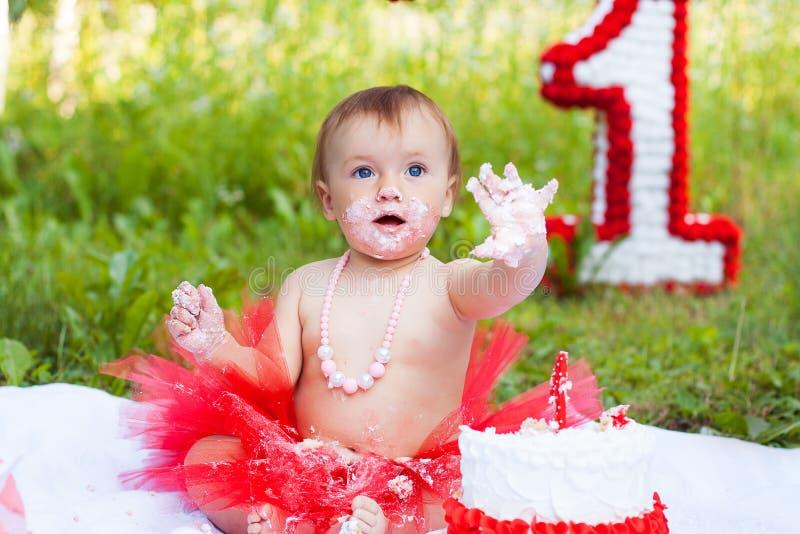 Ein jähriges Kind, das ihren ersten Geburtstagskuchen isst lizenzfreies stockfoto