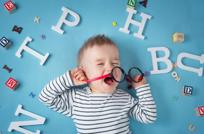 Ein jähriges Kind, das mit Schauspielen und Buchstaben liegt lizenzfreies stockfoto