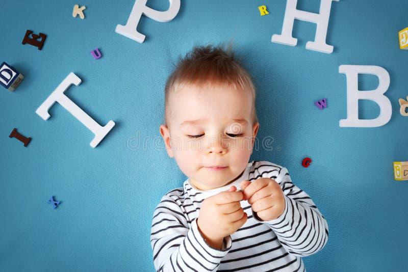 Ein jähriges Kind, das mit Schauspielen und Buchstaben liegt stockbilder