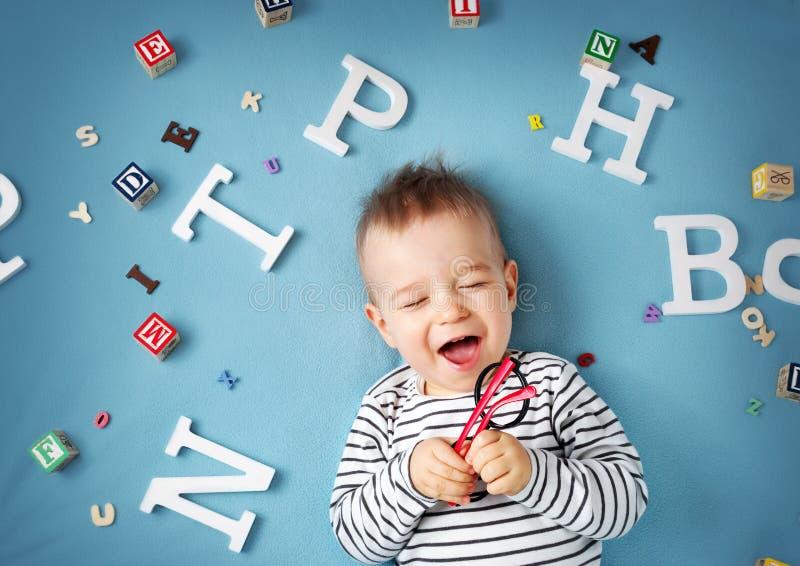 Ein jähriges Kind, das mit Schauspielen und Buchstaben liegt lizenzfreie stockbilder