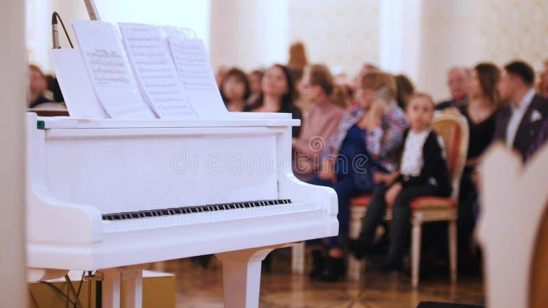 Ein Jazzkonzert im Konzertsaal Klavier auf dem Vordergrund und Publikum auf einem Hintergrund lizenzfreies stockbild
