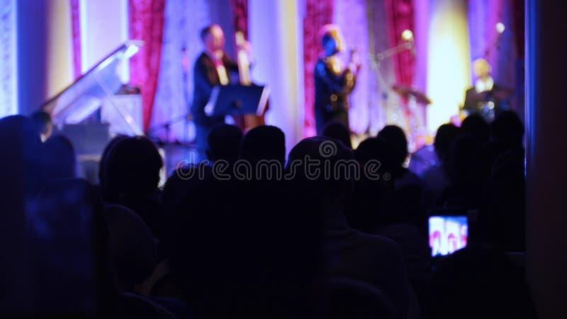 Ein Jazzkonzert im Konzertsaal Leute, die in der Halle sitzen und die Leistung auf einem Video notieren lizenzfreies stockfoto