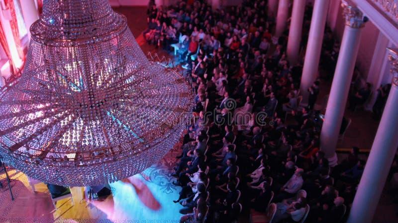 Ein Jazzkonzert im Konzertsaal mit einem großen Kristallleuchter Leute, die auf den Stühlen sitzen stockbild