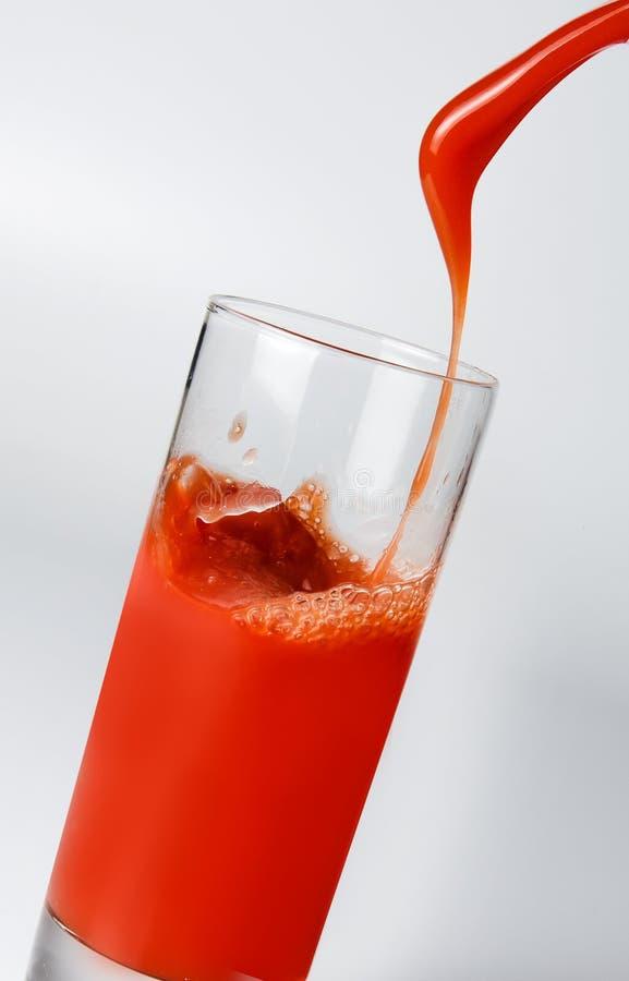 Ein Jet des frischen Tomatensafts ein Glas f?llend Nahaufnahme stockbilder