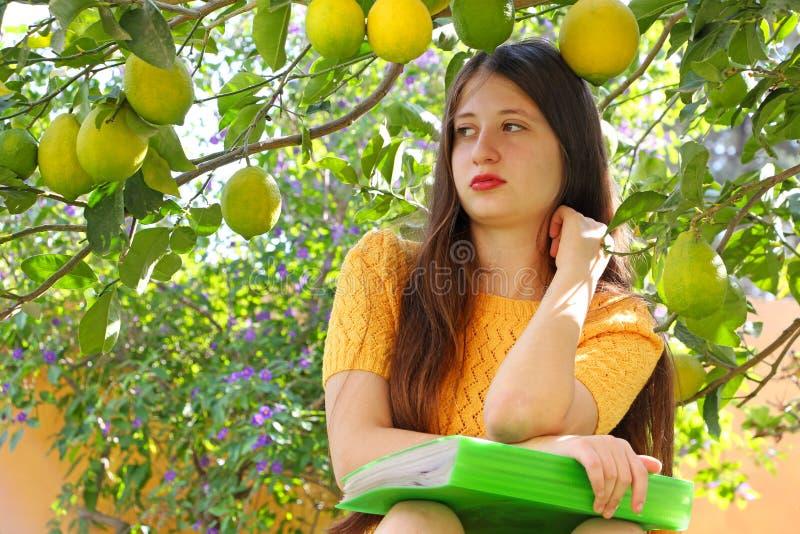 Ein jugendlich Altersmädchen lernt im Garten unter einem Zitronenbaum lizenzfreie stockfotografie
