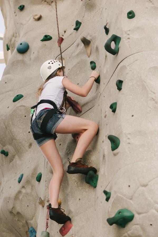 Ein jugendlich Mädchen, das auf einer Felsenwand klettert. stockbild