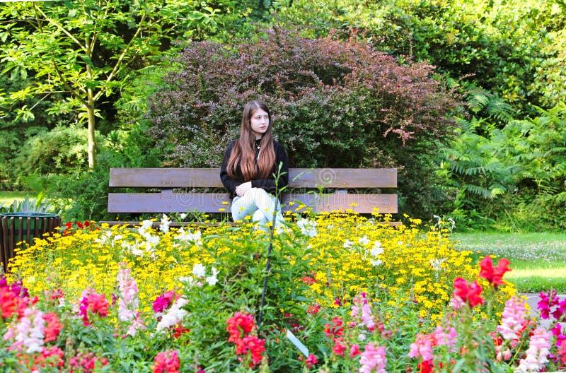 Ein jugendlich Mädchen, das im Garten sitzt stockbilder